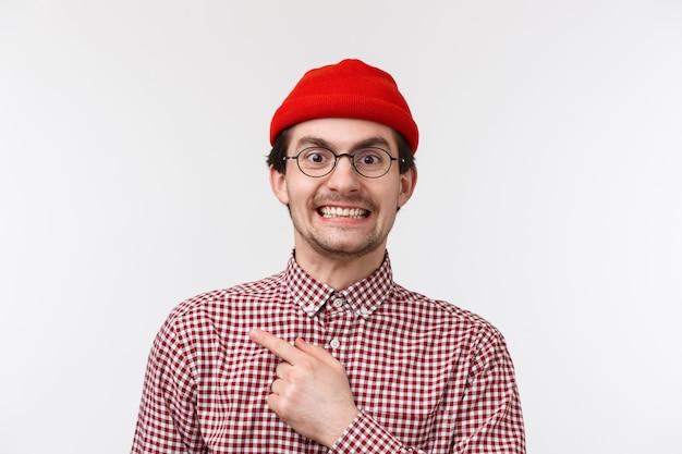 Close-up portrait excité beau et gai jeune homme européen, collègue inviter un ami à rejoindre ses amis au pub après le travail, pointant le doigt dans le coin supérieur gauche