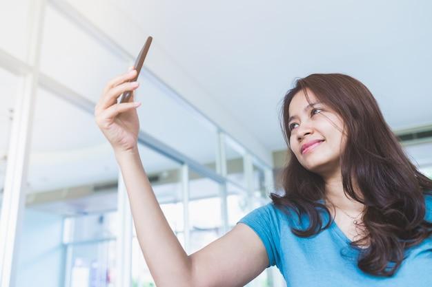 Close up portrait d'une femme asiatique vêtue d'une chemise bleue se tenant debout pour prendre des selfies