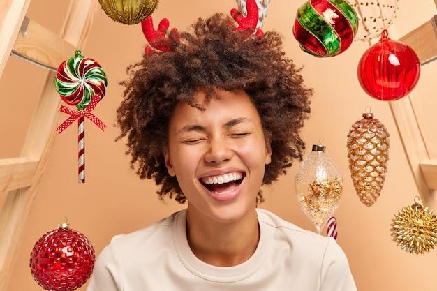 Close up portrait de femme aux cheveux bouclés trop émotive avec un large sourire montre des dents blanches porte des cornes de renne rouge habillé avec désinvolture