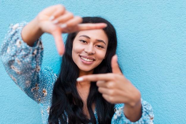 Close-up portrait de femme et cadre fait avec les mains