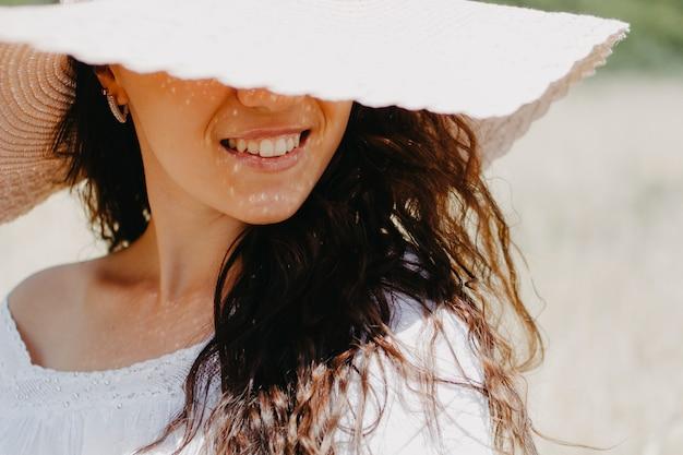 Close-up portrait d'une femme avec un chapeau fermé dans le visage sol dans le cadre seulement sourire.