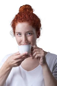 Close-up portrait de fille aux cheveux rouges avec des taches de rousseur en regardant la caméra