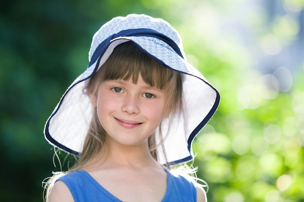 Close-up portrait de fillette souriante heureuse dans un grand chapeau. enfant s'amuser en plein air en été.