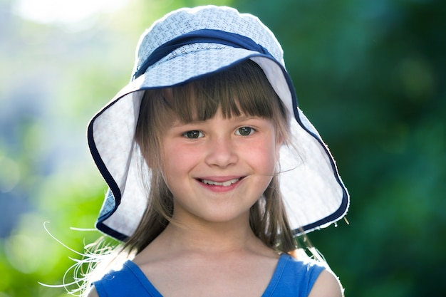 Close-up portrait de fillette souriante heureuse dans un grand chapeau.