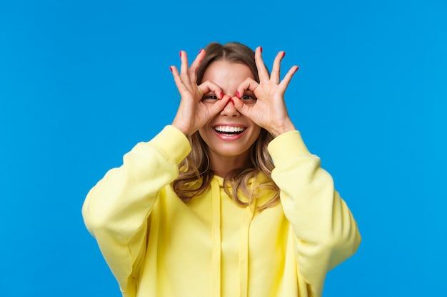 Close-up portrait gai et ludique jolie fille blonde faisant des lunettes avec les doigts, regardant à travers avec un sourire amusé, heureux et divertissant, debout sans soucis sur le mur bleu