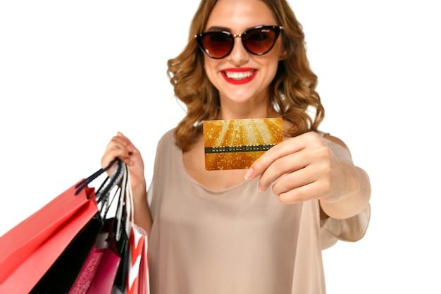 Close-up portrait d'heureuse jeune femme brune à lunettes de soleil tenant une carte de crédit or