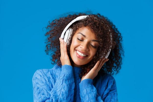 Close-up portrait heureux souriant, romantique et tendre femme afro-américaine appréciant l'écoute de la musique dans les écouteurs, inclinez la tête fermer les yeux rêveurs et souriant ravi, mur bleu.