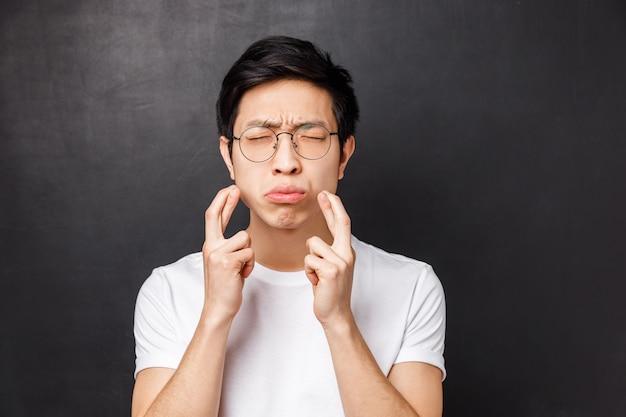 Close-up portrait d'homme asiatique embarrassé et prudent, inquiet en t-shirt blanc