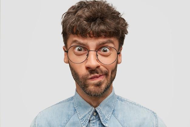 Close up portrait d'homme barbu perplexe regarde dans la perplexité, porte les lèvres, a une expression nerveuse mécontentement