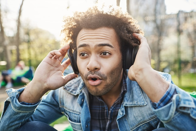 Close-up portrait de jeune afro-américain excité et fasciné avec une coiffure afro, assis en partk et écoutant de la musique dans des écouteurs tout en les tenant avec les mains.