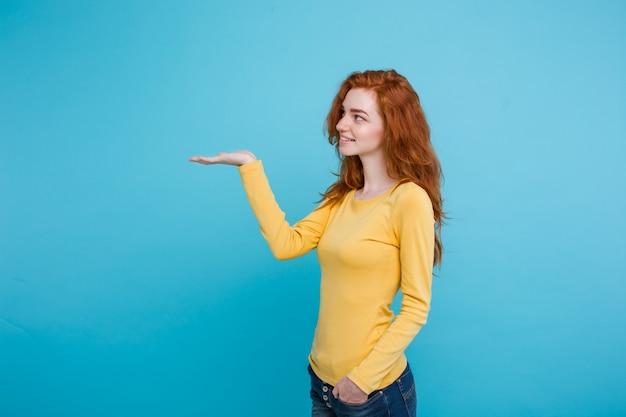 Close up portrait jeune belle fille sexy redhair heureuse avec quelque chose et pointer le doigt. blue pastel background. espace de copie.