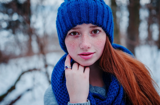 Close up portrait de jeune fille cheveux roux avec des taches de rousseur porter au bonnet de laine bleu et une écharpe en journée d'hiver.