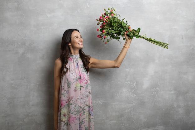 Close-up portrait de jolie jeune femme en robe d'été tenant le bouquet de roses