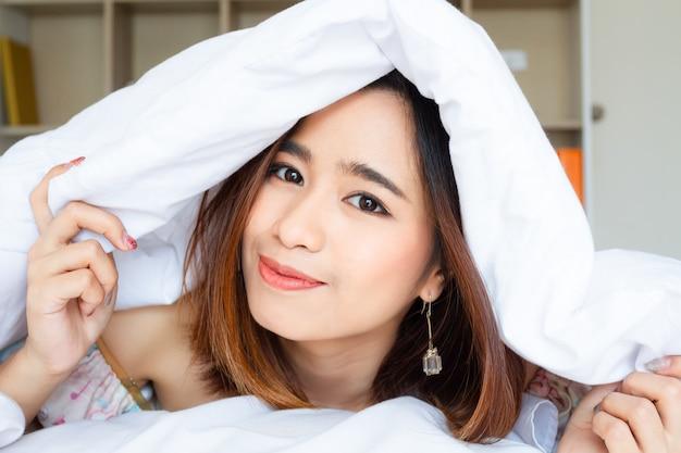 Close up portrait jolie jeune femme sous une couverture blanche