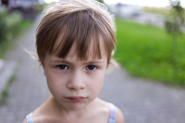 Close-up portrait de jolie jeune petite blonde pâle malheureuse de mauvaise humeur enfant fille sans amis, regardant tristement.