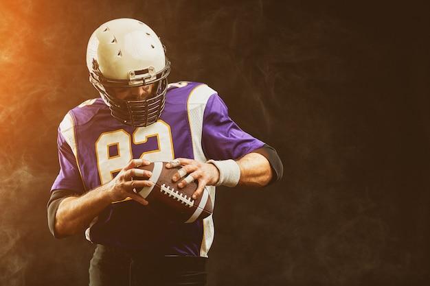 Close-up portrait, joueur de football américain, barbu sans casque avec le ballon dans ses mains. le concept du football américain, la colère sportive, le gros plan, l'éclairage spécial