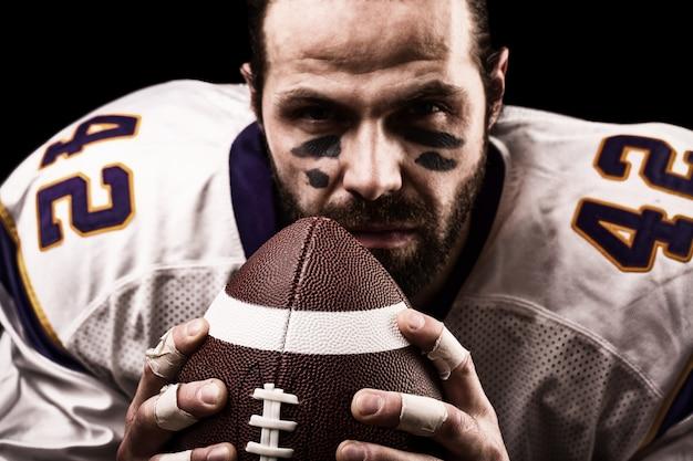Close-up portrait, joueur de football américain, barbu sans casque avec le ballon dans ses mains. concept de football américain, patriotisme, gros plan.