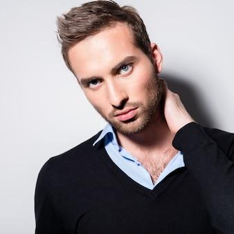 Close-up portrait de mode de jeune homme en pull noir pose sur le mur avec des ombres de contraste
