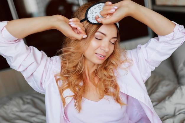 Close up portrait de mode de vie de femme heureuse avec un sourire candide posant dans un masque pour les yeux dans la chambre
