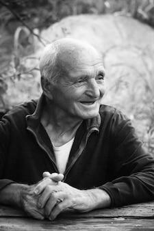 Close-up portrait noir et blanc d'un très vieil homme avec les bras croisés, assis à une table