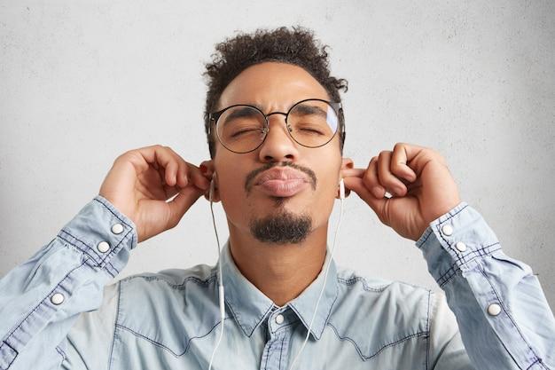 Close up portrait of afro american man avec moustache et barbe porte chemise en jean et grosses lunettes rondes,