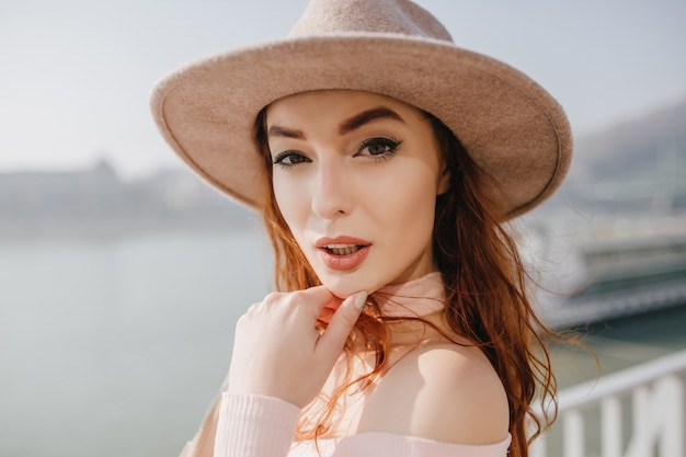 Close-up portrait of amazing ginger woman in beige fedora debout sur la mer