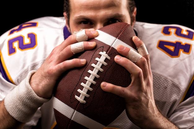 Close up portrait of american football player qui embrasse doucement le ballon