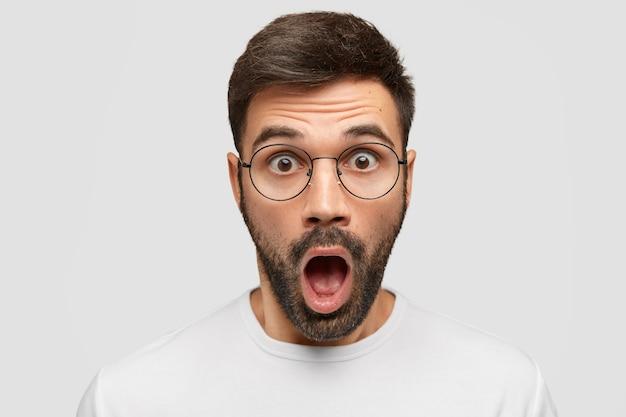 Close up portrait of attractive beared man réagit aux nouvelles soudaines, regarde à travers des lunettes, ouvre largement la bouche