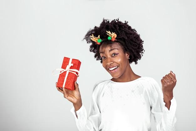 Close up portrait of attractive beautiful girl holding boîte-cadeau dans les mains heureux prêt à le déballer portant chemise décontractée