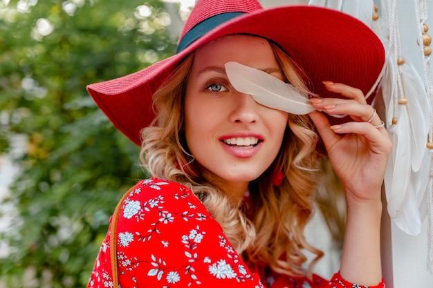 Close-up portrait of attractive blonde élégante femme souriante en paille rouge chapeau et chemisier tenue de mode d'été tenant la peau du visage sensuel sexy plume blanche
