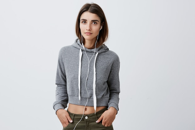 Close up portrait of attractive confiant young caucasian woman with long brown hair in elegant grey hoodie and jeans holding hands in poches, écouter de la musique avec des écouteurs