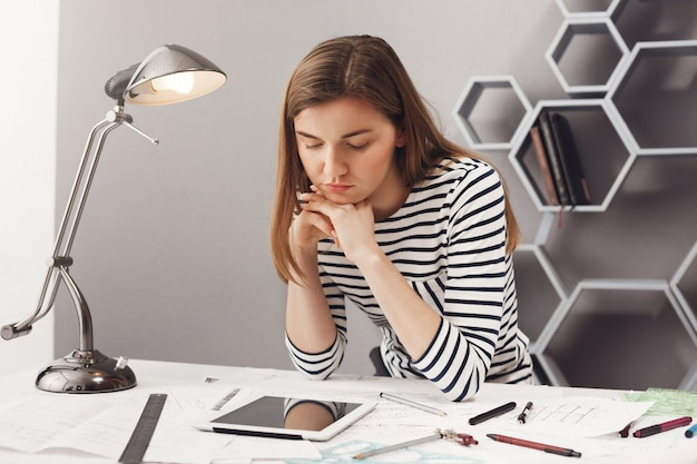 Close up portrait of beautiful young serious female architect student student with brown hair in striped look, holding head with hands, looking in digital tablet with fat face expression, looking for exampl