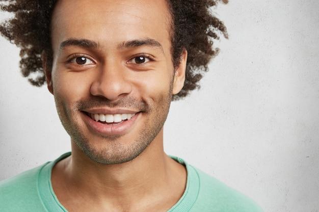 Close up portrait of bel homme barbu avec des poils et des cheveux bouclés touffus, sourit largement