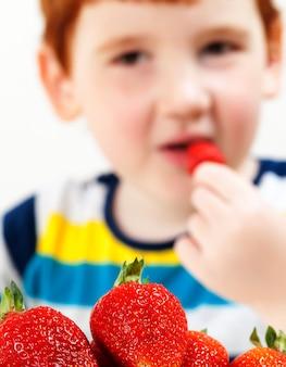 Close up portrait of boy mange des fraises