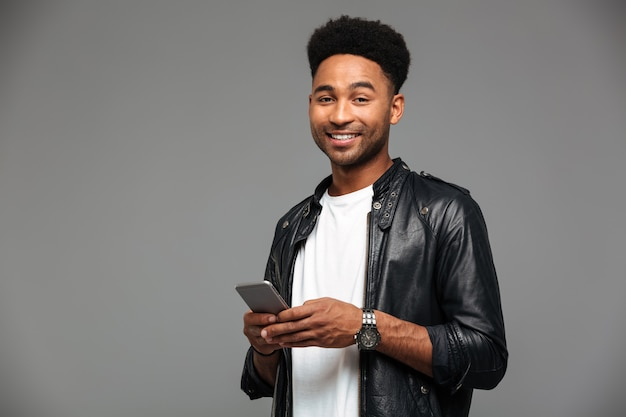 Close-up portrait of cheerful african guy with stylich haircut holding mobile phone, looking