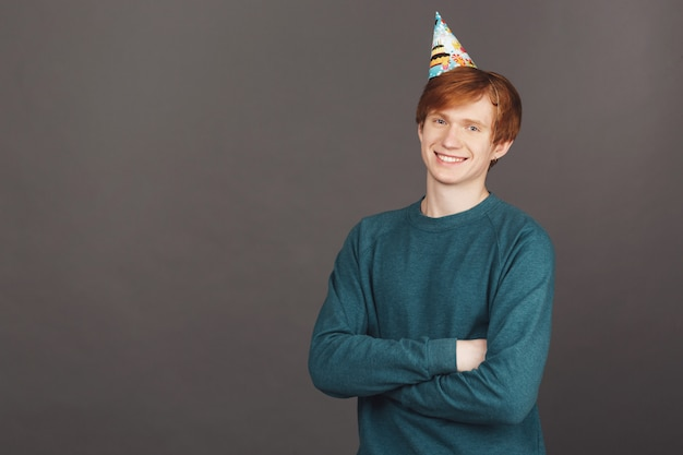 Close up portrait of cheerful male with ginger hair in green sweater and party cap smiling, crossing hands
