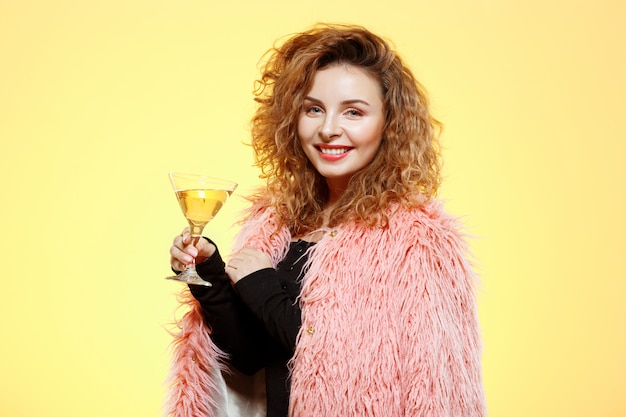 Close up portrait of cheerful smiling beautiful brunette brunette curly girl in pink fur coat holding cocktail glass over yellow wall