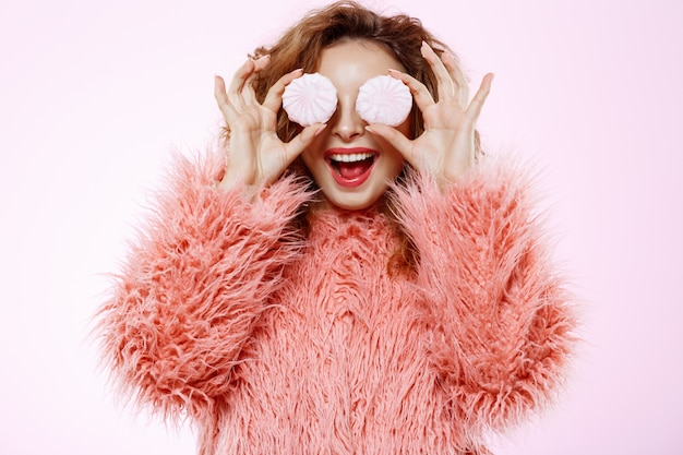 Close up portrait of cheerful smiling beautiful brunette curly girl in pink fur coat holding guimauve sur mur blanc