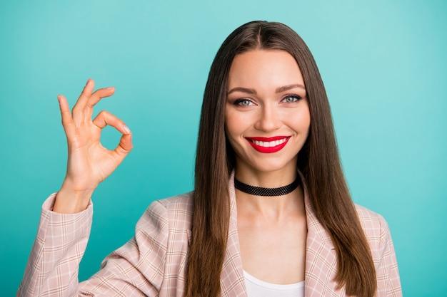 Close-up portrait of cheery girl montrant ok-sign isolé sur un mur de couleur turquoise