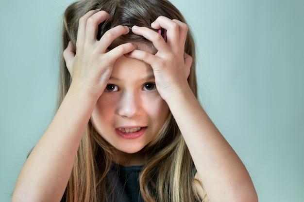 Close-up portrait of choqué malheureuse petite fille aux cheveux longs, tenant sa tête dans les mains.