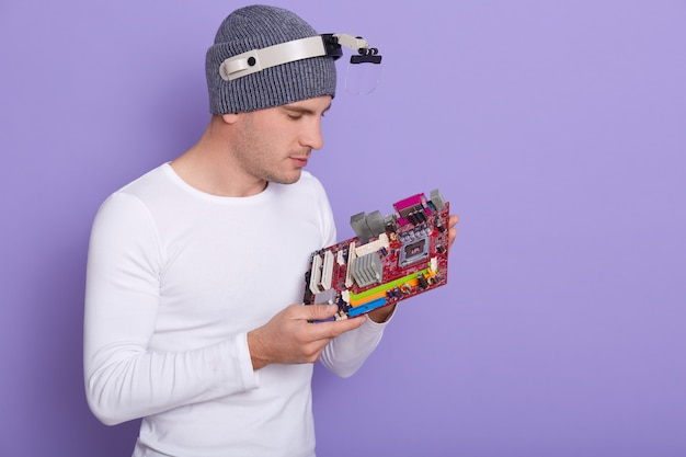 Close up portrait of concentré ingénieur en électronique avec loupe sur sa tête