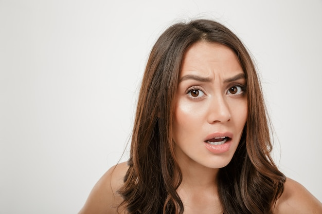 Close up portrait of confused caucasian woman looking on camera in perplexité avec des expressions faciales, isolated over white