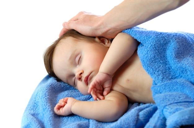 Close-up portrait of a cute little girl dormant dans les bras de sa maman dans une serviette bleue sur une scène blanche
