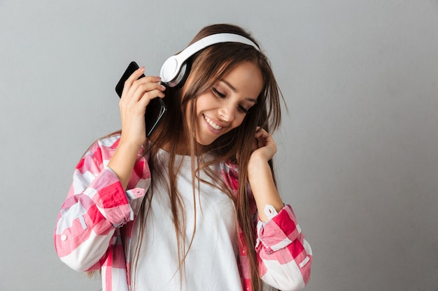 Close-up portrait of dancing young happy woman listen music with white headphones