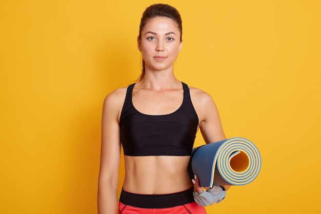 Close up portrait of fitness woman ready for workout, slim girl standing against yellow studio wall and holding yoga mat