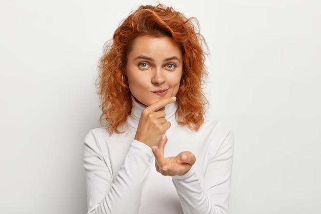 Close up portrait of ginger female étend la paume, porte les lèvres et tient le menton, regarde droit, a une beauté naturelle, vêtue d'un col roulé blanc, décide quelque chose, pose à l'intérieur