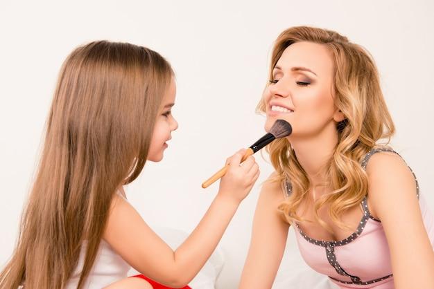 Close up portrait of girl appliquer de la poudre sur le visage de sa mère