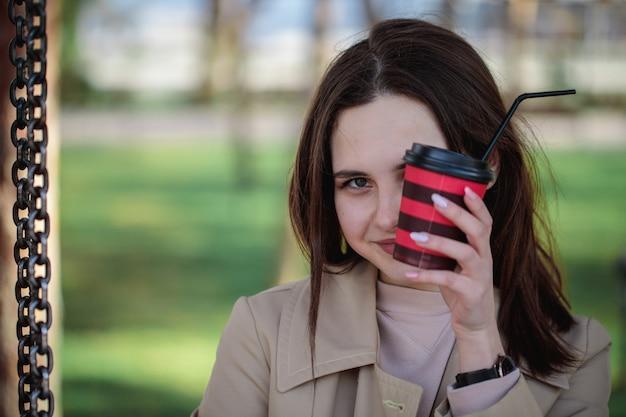 Close-up portrait of a girl, une partie de son visage recouvert d'un verre avec une paille. verre jetable avec une boisson dans des mains féminines.
