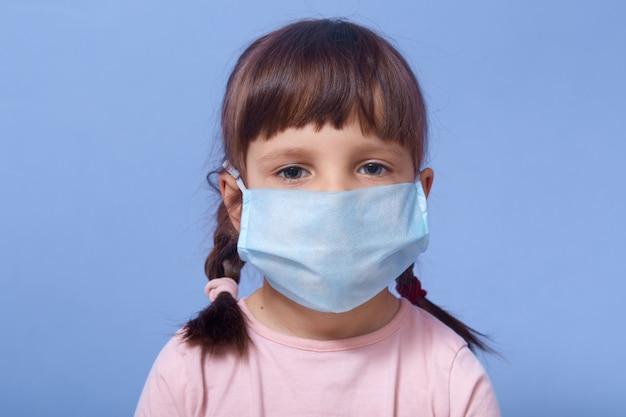 Close up portrait of grave sweet petite fille portant un masque médical, regardant directement la caméra ar