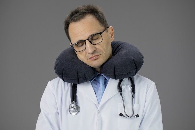 Close-up portrait of handsome adult doctor with travel pillow over neck